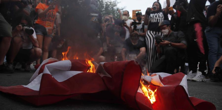 Burning United States flags and demolishing Christopher Columbus statue in Baltimore
