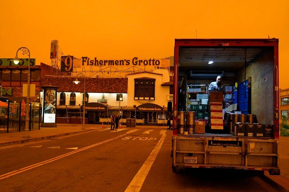 A driver unloads liquor in California's Fisherman's Wharf neighborhood under smoke-darkened skies.