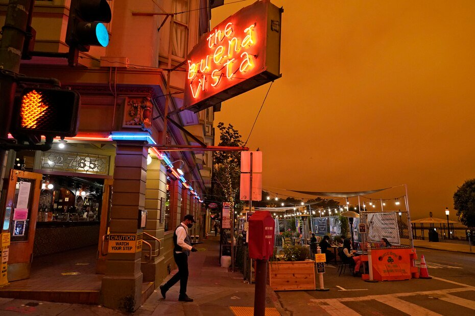 A waiter serves a table at a business in San Francisco under a smoky sky.