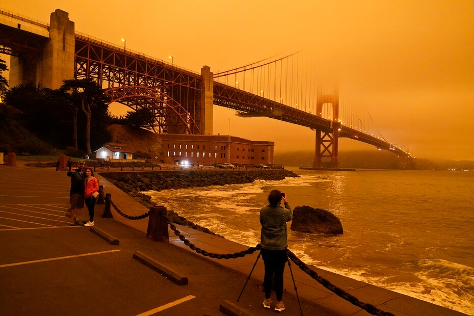 Citizens stop at Fort Point to take photos of the smoke-covered Golden Gate Bridge.
