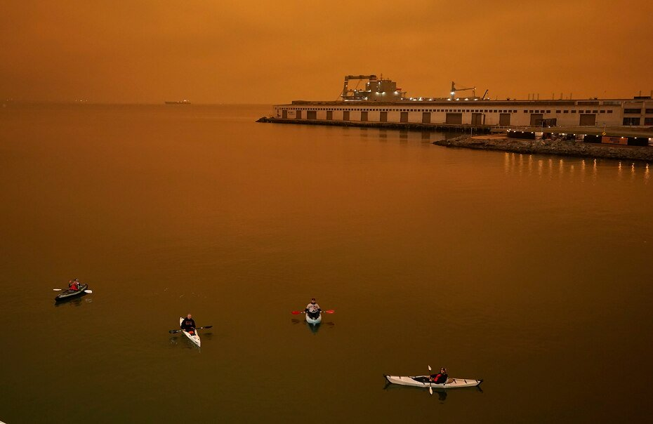 Several people in kayaks paddle into McCovey Cove during wildfires.