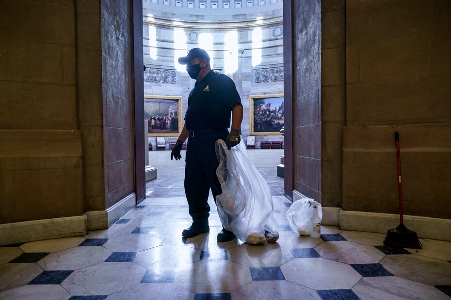 A federal employee cleans the area outside the office of House Speaker Nancy Pelosi, one of which was invaded by the rioters.