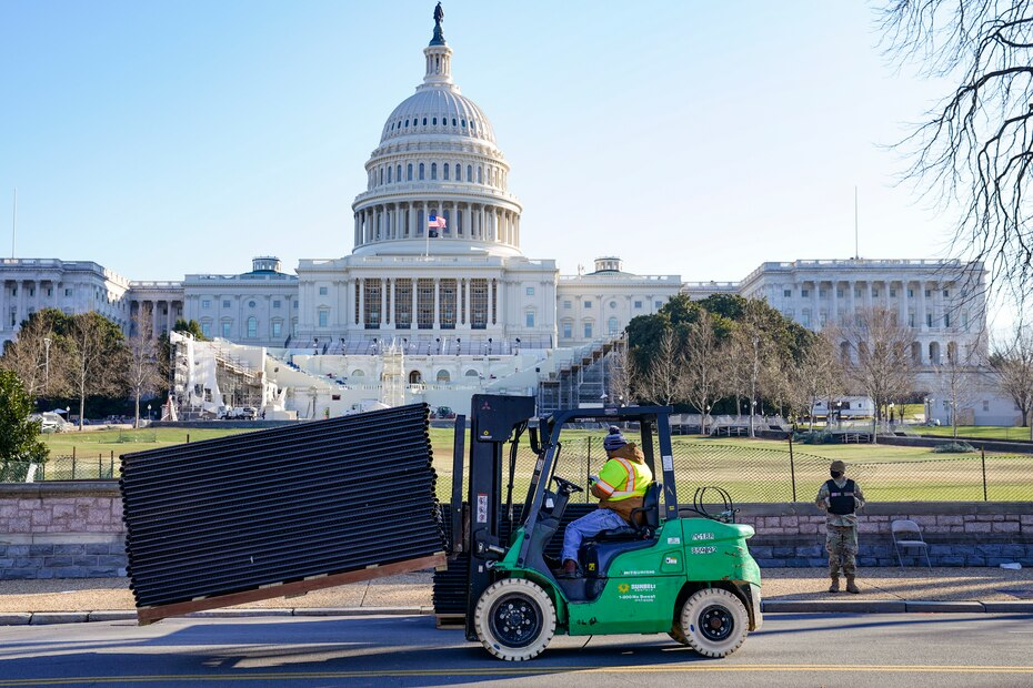 A National Guard soldier stands guard on a quiet Capitol as maintenance workers erected a security fence around the perimeter.