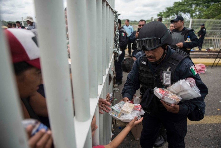 A Mexican agent gives food to Hondurans who are trapped on a bridge without being able to cross.