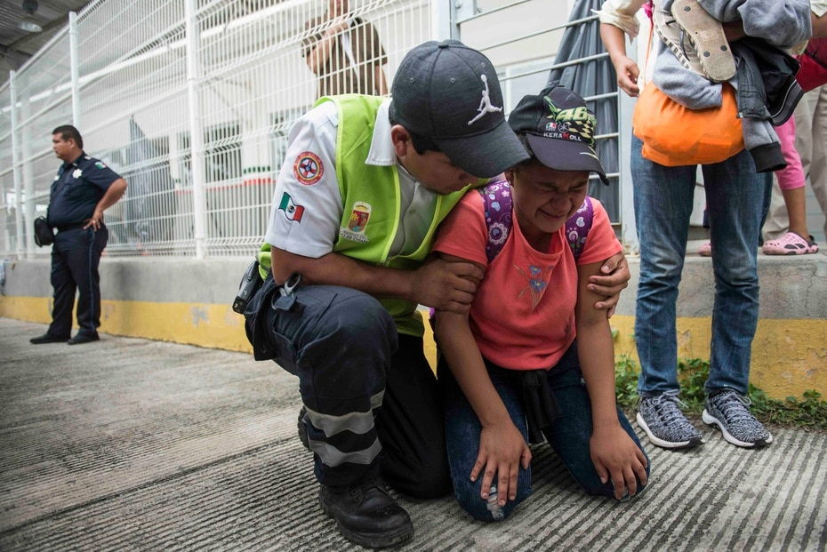 A migrant from Honduras is helped by a paramedic from Mexico after her mother fainted while trying to cross.
