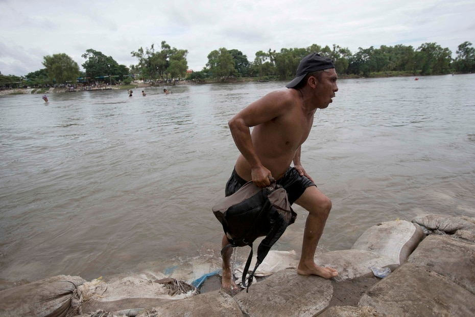 This man emerges victorious from the Suchiate River after crossing it.