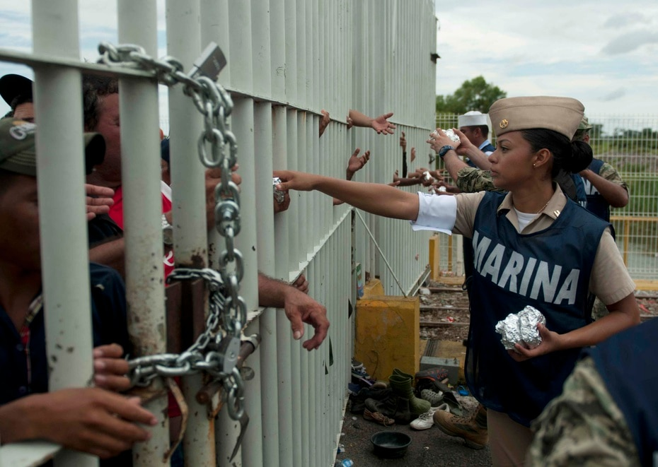An officer gives food to migrants through a gate.