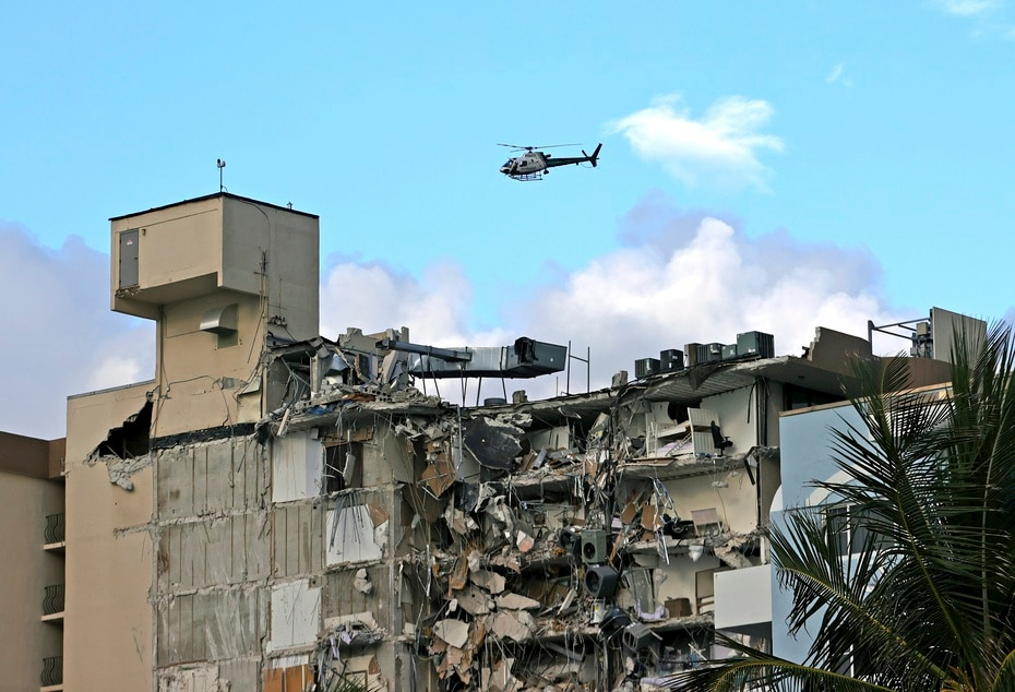 A Miami-Dade Fire Department helicopter flies over the area where the condominium that partially collapsed this morning is located.
