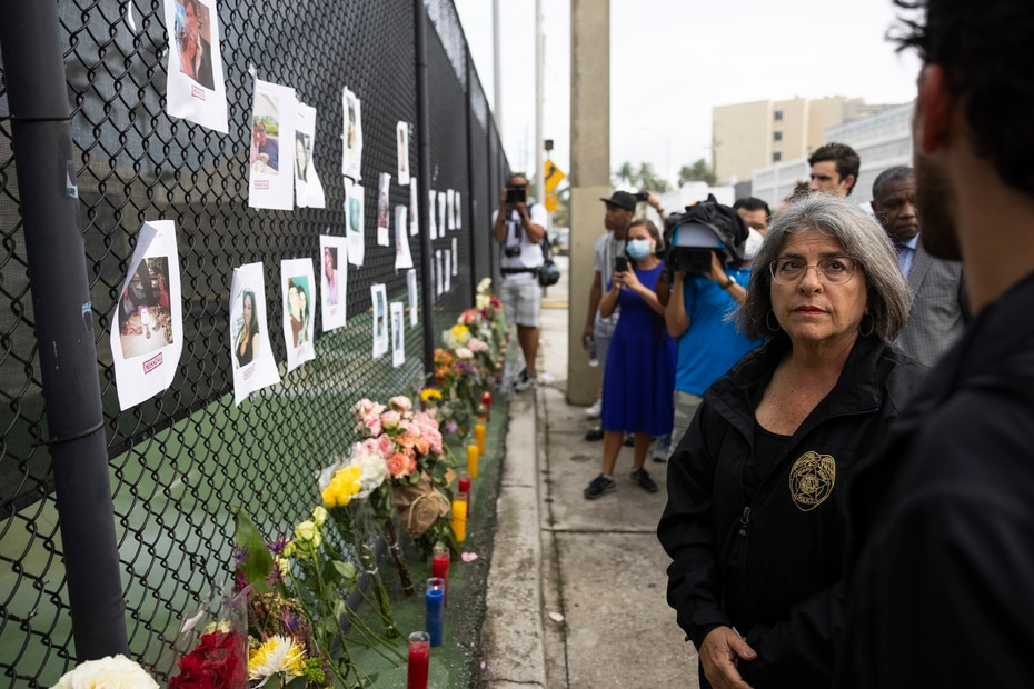 In the photo, Miami Mayor Daniella Levine comes to a makeshift memorial near the scene where families have posted photos of their missing.