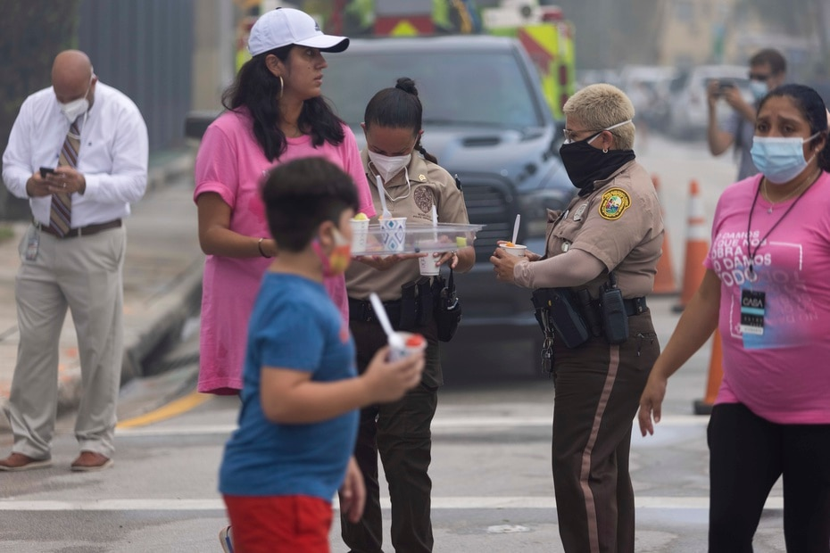 In the photo, volunteers bring food and drink to first responders.