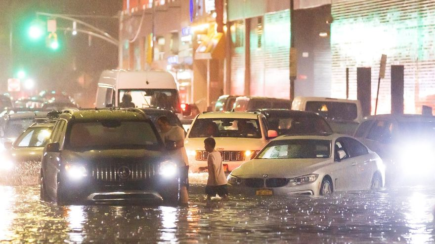 Cars stuck on a street flooded by heavy rain in the Queens, New York area.
