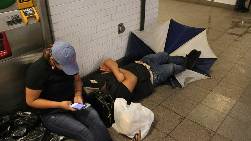 People sitting on the ground in a subway station after heavy rains cause very limited train service.