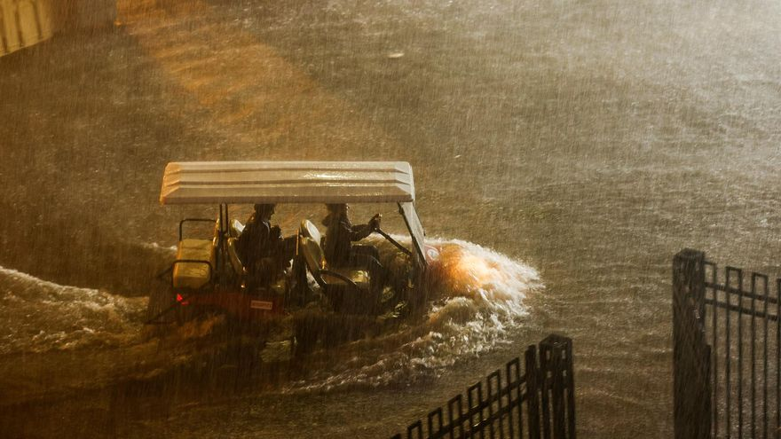 A golf cart travels along a flooded driveway at the Billie Jean King National Tennis Center.