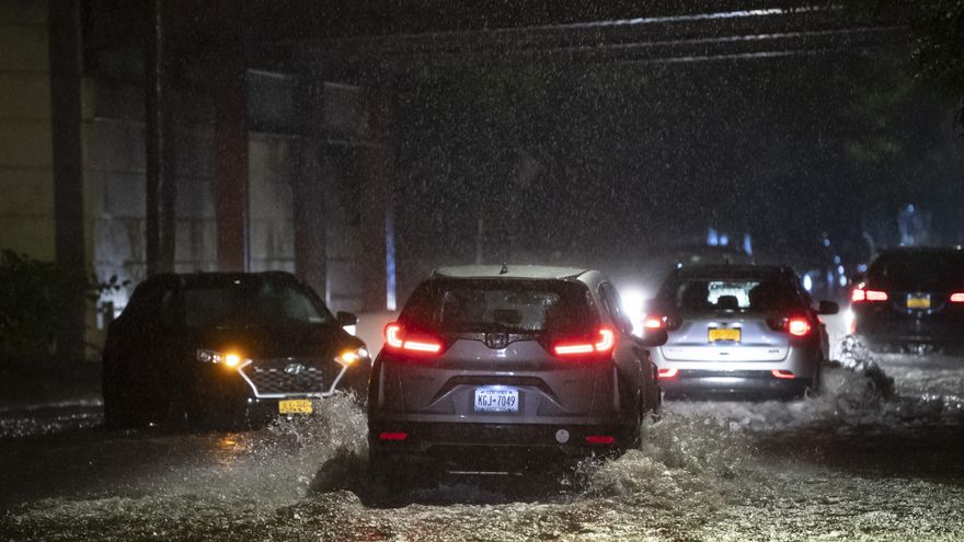 Cars driving down a flooded street in Staten Island, New York.